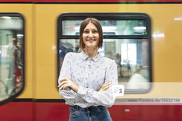Junge Frau am Bahnhof mit verschwommenem Zug als Hintergrund