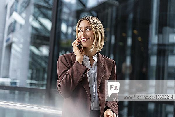 Lächelnde junge Geschäftsfrau am Telefon in der Stadt