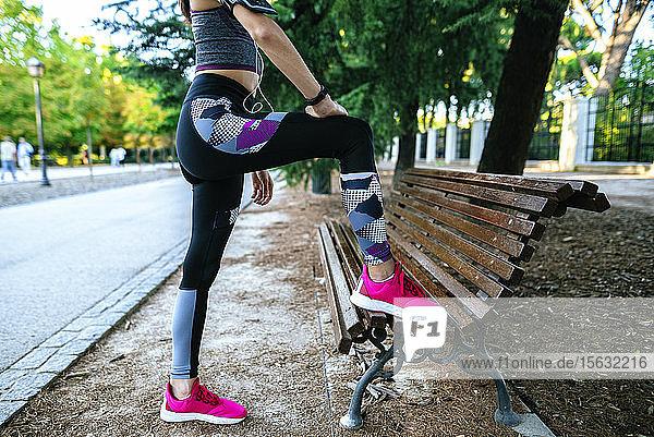 Der Körper einer Frau beim Sport auf einer Parkbank