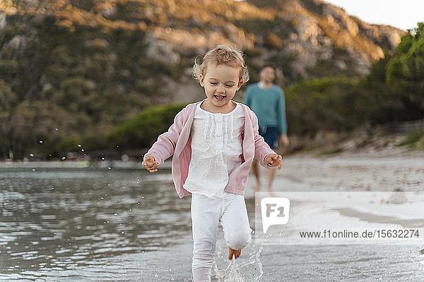 Glückliches Mädchen rennt am Meeresufer mit dem Vater im Hintergrund