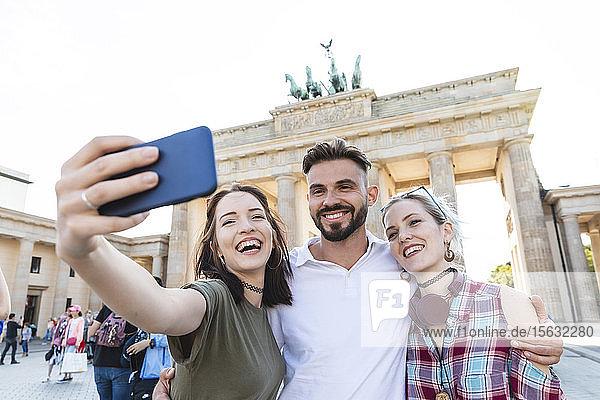 Porträt von drei glücklichen Freunden  die sich mit dem Handy vor dem Brandenburger Tor in Berlin selbstständig machen