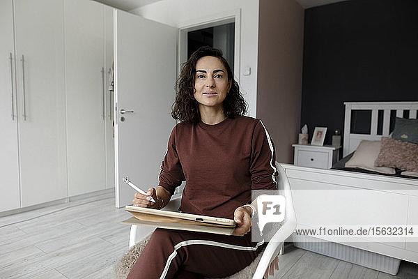 Weibliche Webdesignerin benutzt Tablet zu Hause