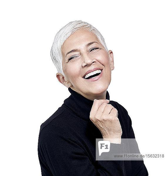 Porträt einer lachenden  reifen Frau mit kurzen  grauen Haaren und schwarzem Rollkragenpullover