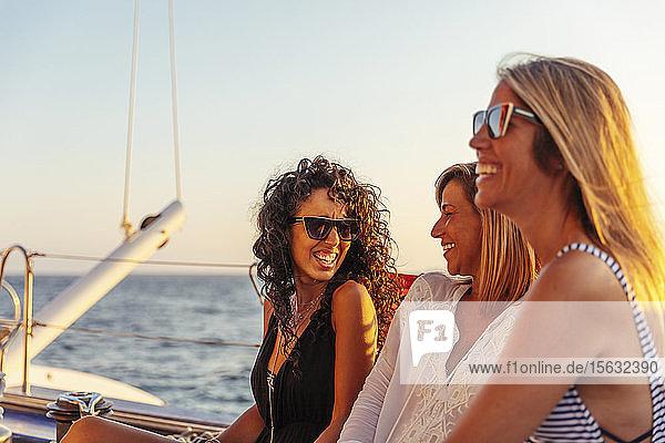 Freunde lachen während der Bootsfahrt im Abendlicht