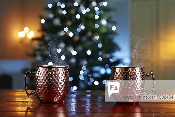 Nahaufnahme von Glühwein auf Holztisch vor beleuchtetem Weihnachtsbaum zu Hause