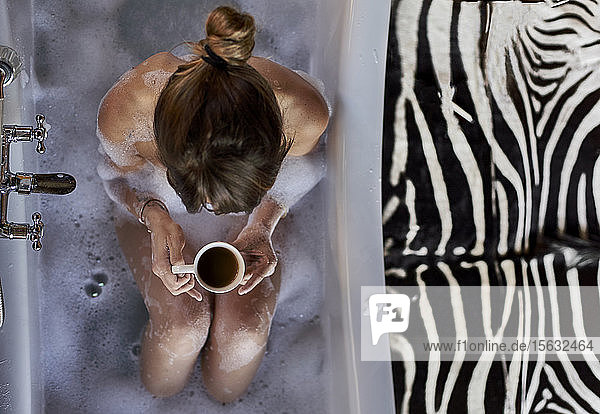 Woman having a relaxing bath and a cup of coffee in the bathtub