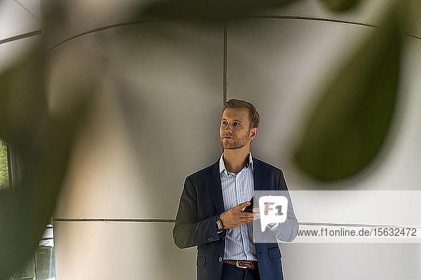 Junger Geschäftsmann hält Smartphone in der Hand  lehnt an einer Wand