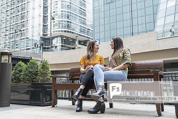 Glückliches lesbisches Paar sitzt auf einer Bank in der Stadt  London  UK