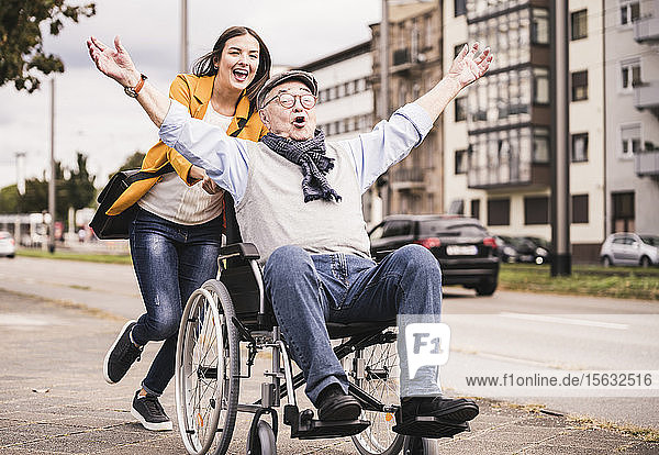 Portrait of young woman pushing senior man in wheelchair on pavement