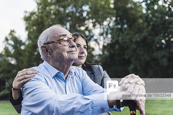 Portrait of senior man man with his granddaughter in a park