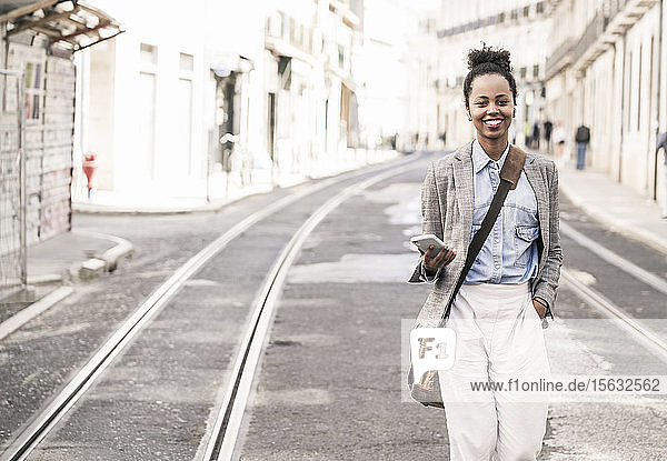 Lächelnde junge Frau mit Handy in der Stadt unterwegs  Lissabon  Portugal