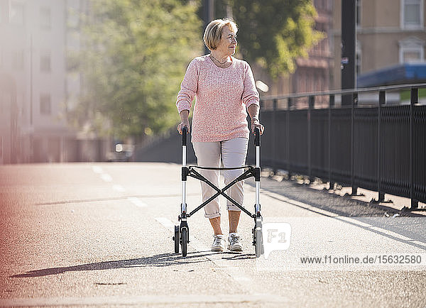 Senior woman with wheeled walker on footbridge