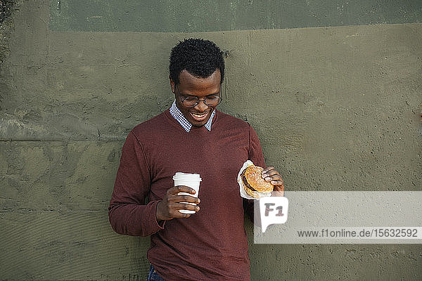 Young man with a chesseburger and coffee to go  portrait