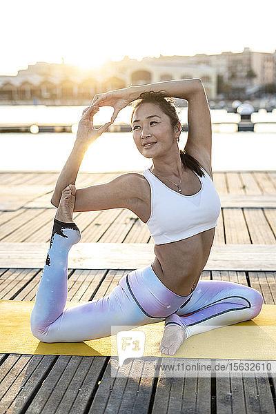 Asiatin  die bei Sonnenuntergang auf einem Pier am Hafen Yoga praktiziert  Schwanenhaltung Asiatin, die bei Sonnenuntergang auf einem Pier am Hafen Yoga praktiziert, Schwanenhaltung