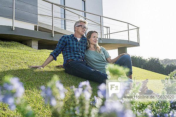 Lächelndes Paar vor ihrem modernen Zuhause