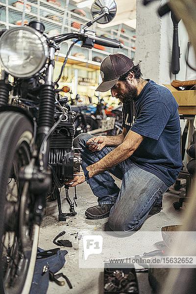 Mechanic in a repair garage repairing a motorcycle