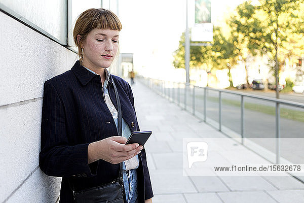 Portrait of strawberry blonde young woman looking at cell phone