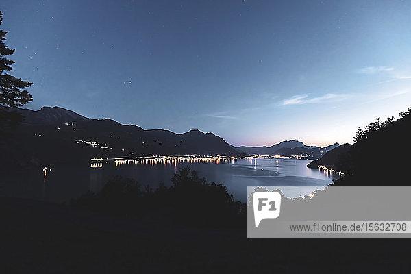 Schweiz  Gersau  Schwyz  Beleuchtete Häuser entlang der Küste des Vierwaldstättersees in der Abenddämmerung
