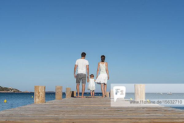 Rückansicht einer Familie  die auf einem Steg am Meer spazieren geht