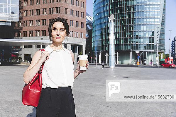 Junge Geschäftsfrau mit Kaffee zum Mitnehmen in der Stadt unterwegs  Berlin  Deutschland