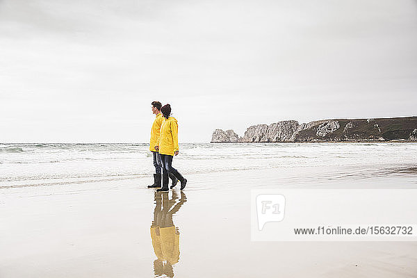 Young woman wearing yellow rain jackets and walking along the beach  Bretagne  France