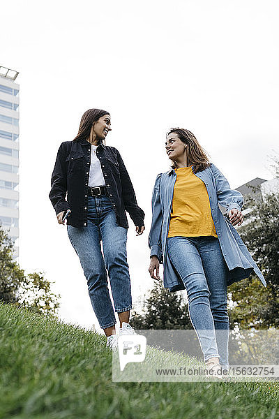 Two friends talking while walking through a park