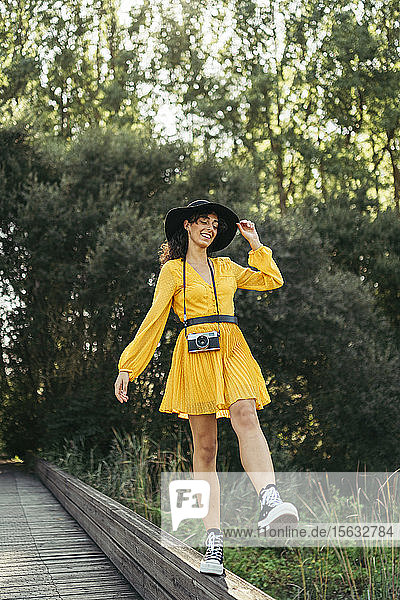 Young woman wearing a black hat and yellow dress with an analog camera on wooden boardwalk