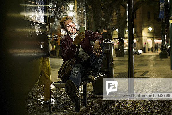 Portrait of laughing young man sitting at bus stop by night using smartphone  Lisbon  Portugal