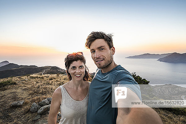 Couple taking a selfie at sunset  Belvedere de Saliccio  Piana  Corse-du-Sud  Corsica  France