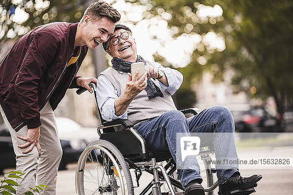 Laughing senior man in wheelchair and his adult grandson looking together at smartphone having fun