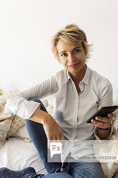 Porträt einer lächelnden reifen Frau  die zu Hause auf dem Bett sitzt und ein Smartphone hält