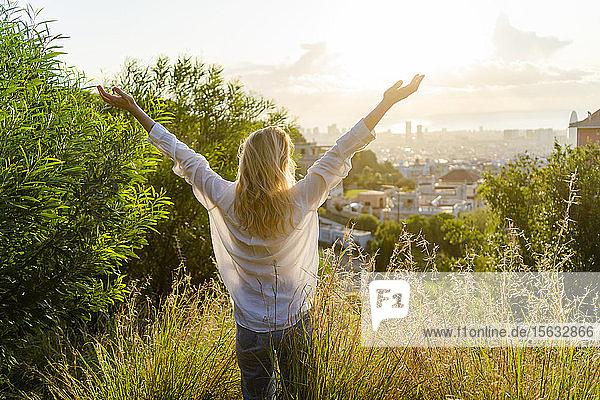 Rückansicht einer sorglosen jungen Frau  die bei Sonnenaufgang über der Stadt steht  Barcelona  Spanien