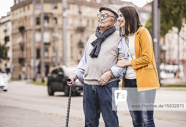 Erwachsene Enkelin hilft ihrem Großvater beim Spaziergang mit einem Spazierstock