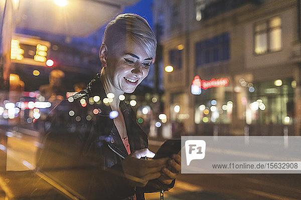Porträt einer lächelnden blonden Frau an der Straßenbahnhaltestelle mit Blick auf das Mobiltelefon  Berlin  Deutschland