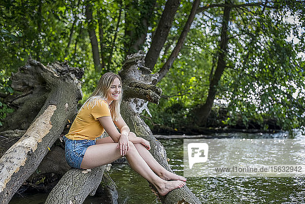 Smiling woman sitting on a tree trunk at lakeshore