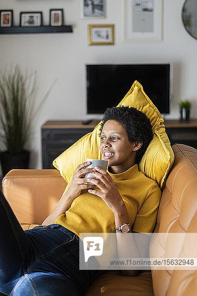 Entspannte junge Frau liegt zu Hause auf der Couch und hält Becher