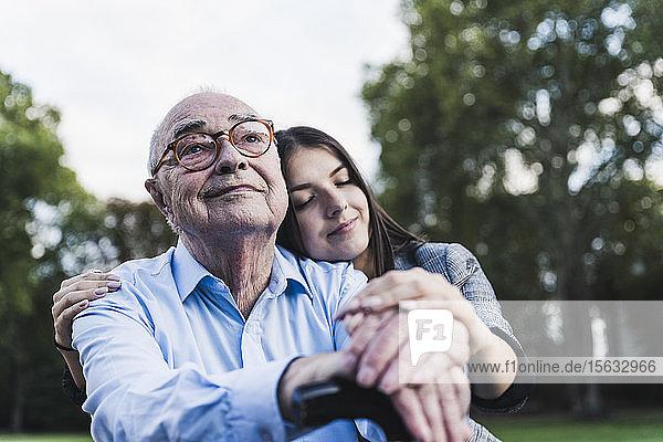 Porträt eines älteren Mannes mit seiner Enkelin in einem Park