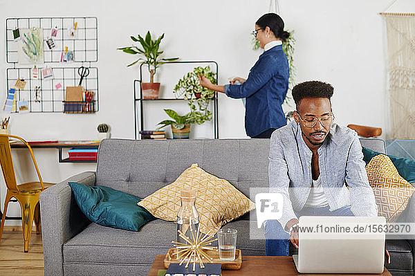 Multiethnisches Paar verbringt Zeit zusammen im Wohnzimmer  Mann benutzt Laptop