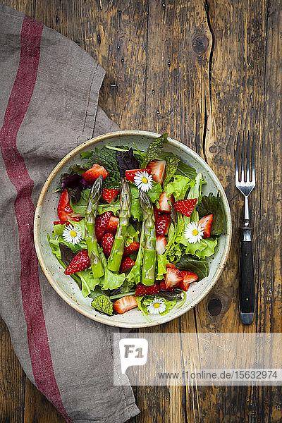 Nahaufnahme von Salat mit grünem Spargel  Erdbeeren und Gänseblümchen