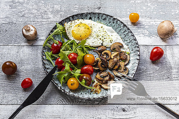 Low carb breakfast with fried egg  mushrooms  rocket and tomatoes
