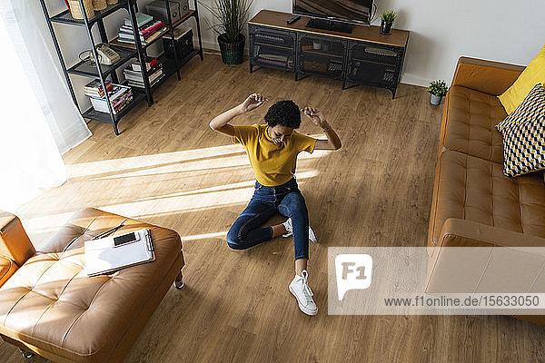 Excited young woman sitting on the floor at home