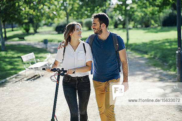 Happy couple with electric scooter in a city park