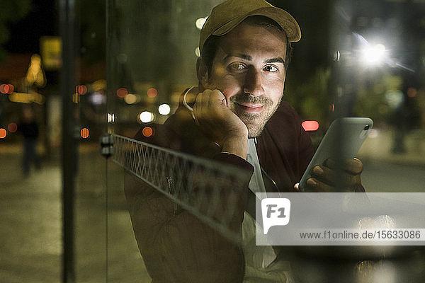 Porträt eines lächelnden jungen Mannes mit Smartphone  der nachts an einer Bushaltestelle wartet  Lissabon  Portugal