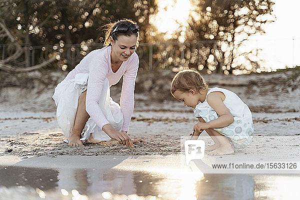 Glückliche Mutter mit Tochter spielt mit Sand am Strand