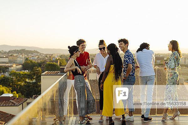 Gruppe glücklicher multiethnischer Freunde feiert abends eine Party