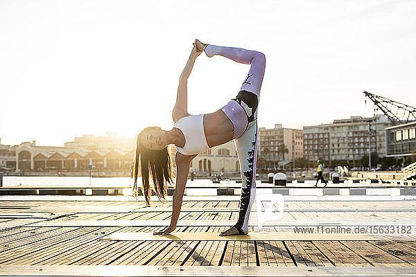 Asiatische Frau  die bei Sonnenuntergang auf einem Pier am Hafen Yoga praktiziert  Tänzer-Pose Asiatische Frau, die bei Sonnenuntergang auf einem Pier am Hafen Yoga praktiziert, Tänzer-Pose