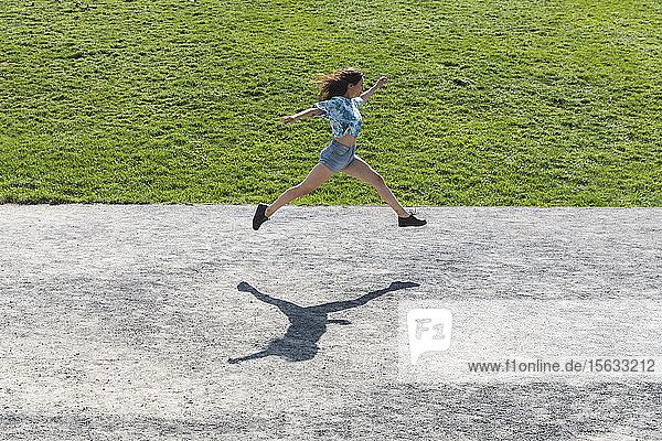 Junge Frau springt und rennt im Sommer im Freien