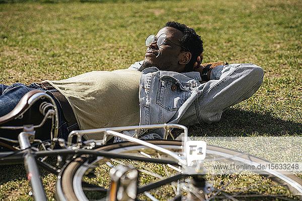Junger Mann mit Fahrrad  entspannend  im Gras liegend