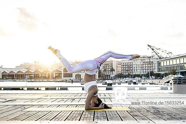 Asiatin  die bei Sonnenuntergang auf einem Pier im Hafen Yoga praktiziert  Kopfstand mit Spalt Asiatin, die bei Sonnenuntergang auf einem Pier im Hafen Yoga praktiziert, Kopfstand mit Spalt