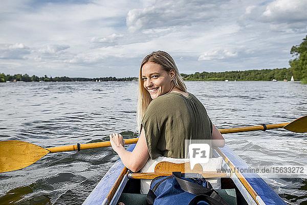 Lächelnde Frau paddelt auf einem See